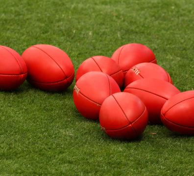 AFL Footballs on a Grass Field