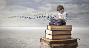 A little kid dressed in an elegant way is sitted on the top of a pile of books, reading something on a tablet